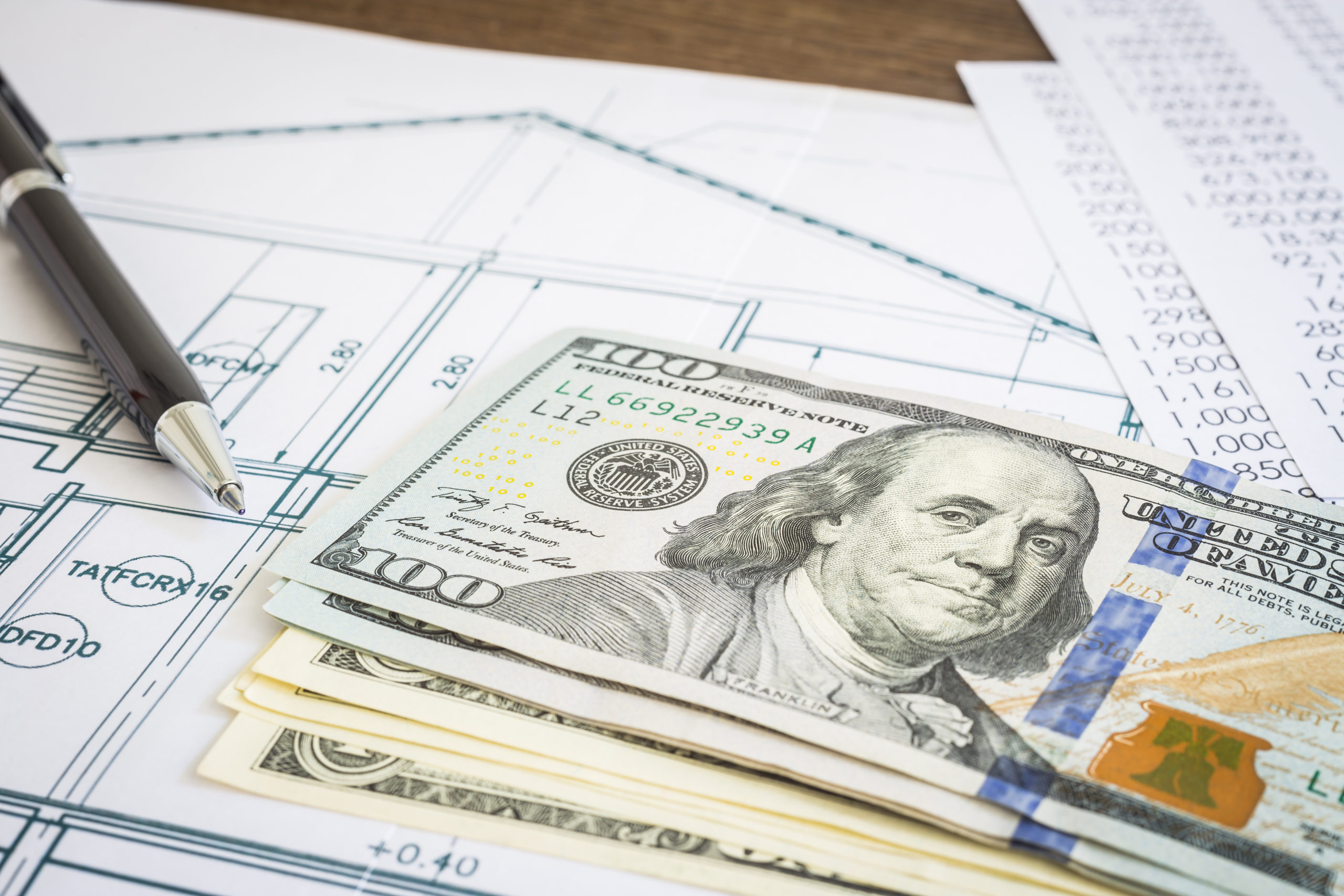 New dollar banknotes or money, house blueprint floor plan, paperwork and black pen put on wooden table. Concepts of construction budget, mortgage, home loan and refinance.