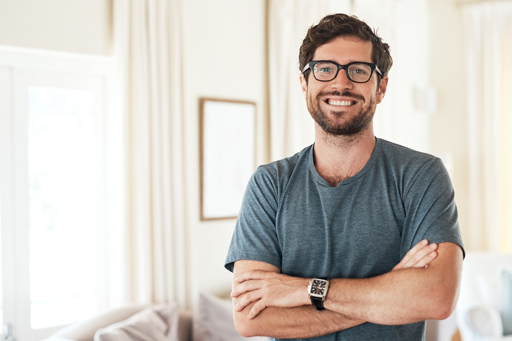 male with glasses standing in home