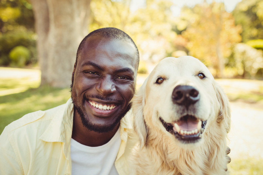 male smiling with golden retriever dog